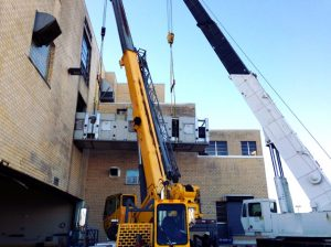 Removing one of seven (7), 40' long 42,000 lb. bakery oven sections from upper floor of bakery using two cranes