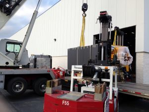 40,000# Injection blow molding machine unloaded with crane and Versa-Lifts, dollied through plant and placed in location