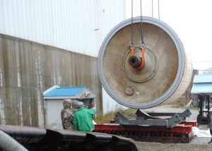 Lowering 156,000 lb., 18' diameter x 25 long Yankee Dryer from Lincoln, ME tissue mill onto shipping cradles set on sliders. After dryer prepared for shipment, sliders were used to transfer the dryer in its shipping cradles onto trailer for shipment