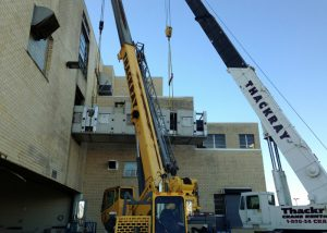 Removing one of seven (7), 40' long 42,000# bakery oven sections from upper floor of bakery using two cranes