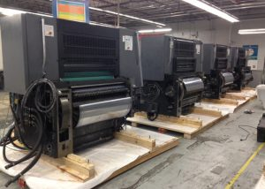 Printing press line in the staging process of being crated and packaged for international shipment. We built custom skids for each unit, secured units to the skids, double plastic wrapped, and loaded in a container.