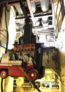 Lowering 14,500# low-headroom lift truck into basement area using a Versa-Lift™ Model 25/35 with boom hoist attachment.  Note the Versa-Lift™ is on a cribbed and plated platform level with the floor, enabling the lift to access the opening
