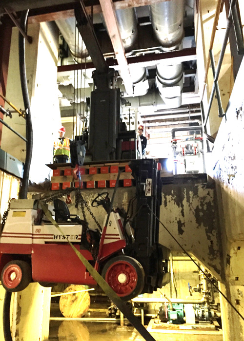 Lowering 14,500 lb. low-headroom lift truck into basement area using a Versa-Lift™ Model 25/35 with boom hoist attachment. Note the Versa-Lift™ is on a cribbed and plated platform level with the floor, enabling the lift to access the opening